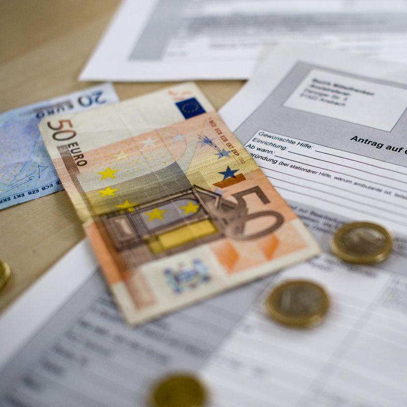 Ein fünfzig Euro Schein und Kleingeld liegen auf einem ausgedrucktem Fomular.