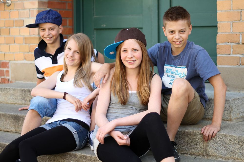 Vier Jugendliche (zwei Jungen, zwei Mädchen) sitzen auf einer Treppe vor einem Haus.