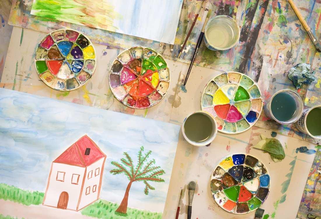 Ein aus Wasserfarben gemaltes Bild und daneben Becher, die mit Wasser gefüllt sind.