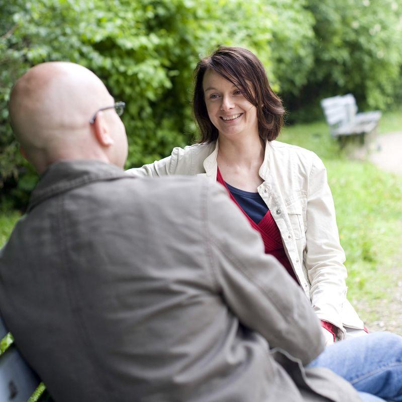 Ein Mann und eine Frau sitzen auf einer Bank und unterhalten sich. Den Mann sieht man nur von hinten.