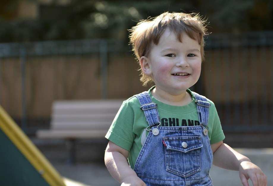 Kleiner Junge in blauer Latzhose und grünem Tshirt