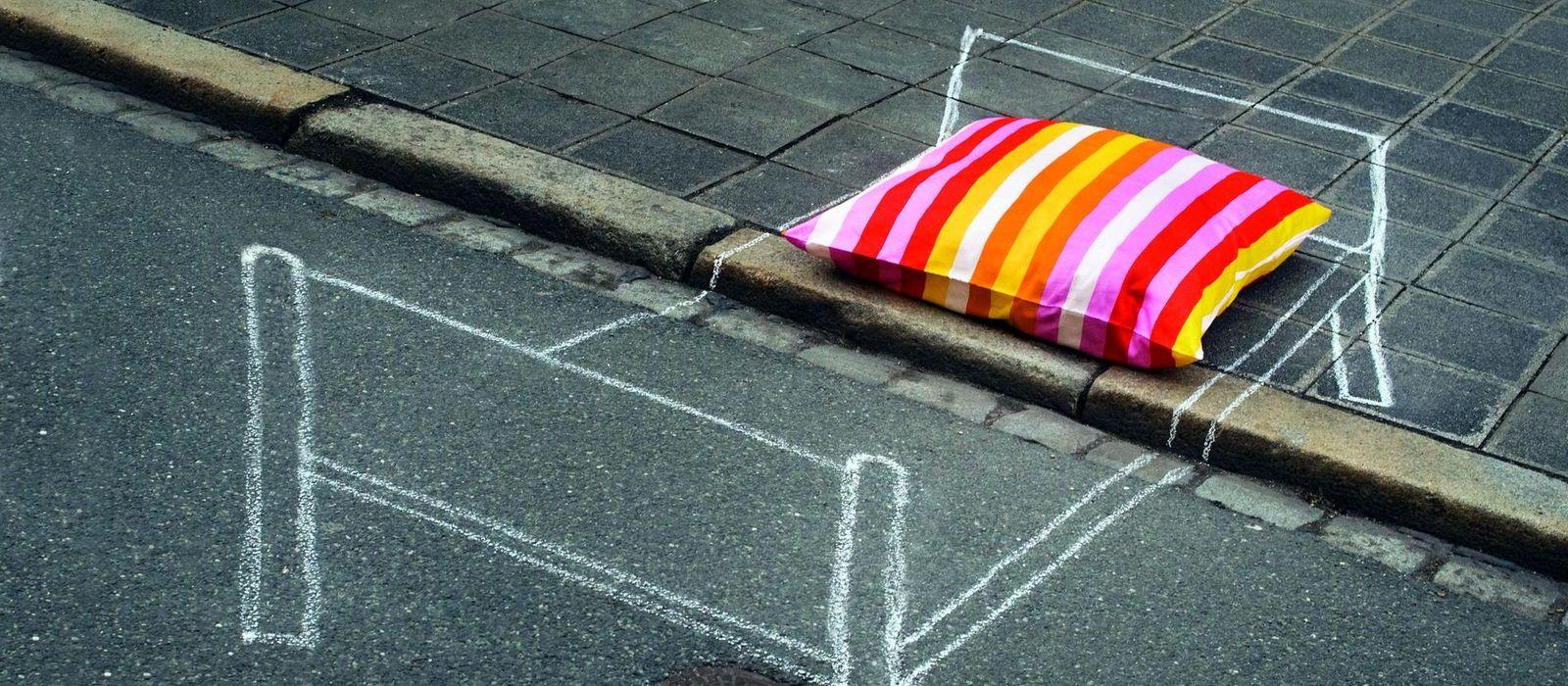 Auf eine Straße ist mit weißer Kreide ein Bett gezeichnet. Auf dem Kreidebett liegt ein bunt gestreiftes Kopfkissen.