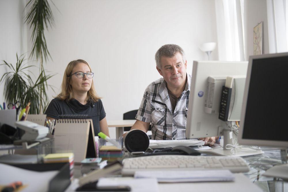 Ein Mann zeigt einer Frau etwas am Computer Monitor.