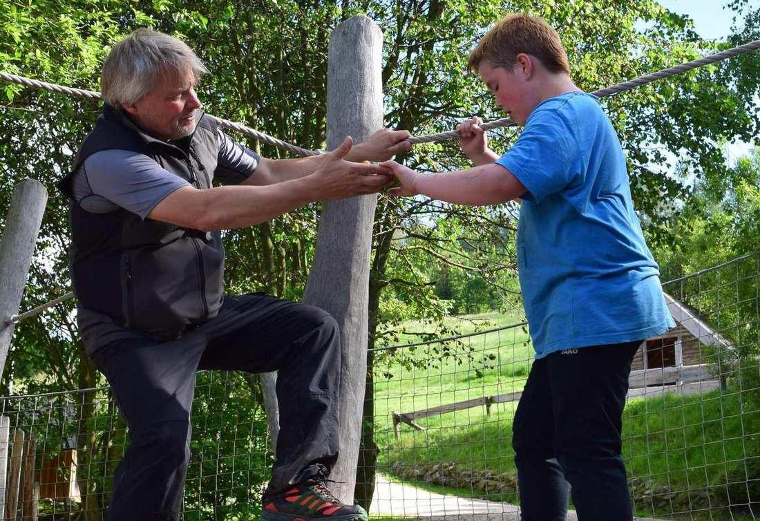 Ein junge im blauen T-Shirt balanciert über ein Seil. Ein Mann streckt ihm hilfreich die Hände entgegen.