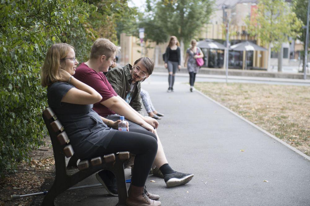 Eine Frau und zwei Männer sitzen auf einer Parkbank und unterhalten sich.