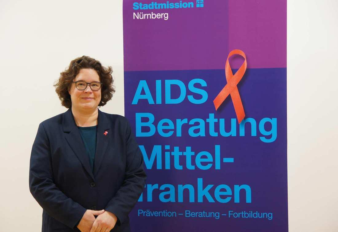 Eine Frau im dunkelblauen Sakko steht neben einem Roll-Up der AIDS-Beratung. Darauf prangt eine große rote AIDS-Schleife.