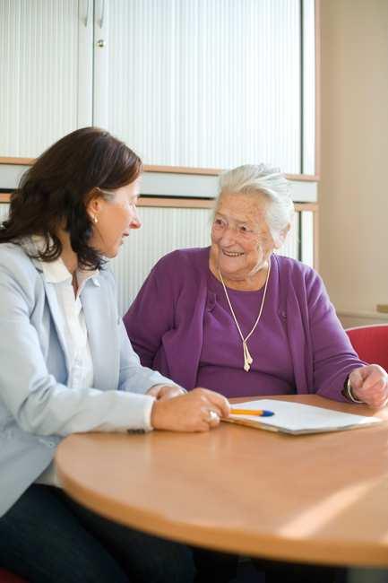 Eine alte Dame sitzt mit einer jüngeren Frau im hellblauen Blazer an einem Tisch. Vor Ihnen Stift und Formulare.