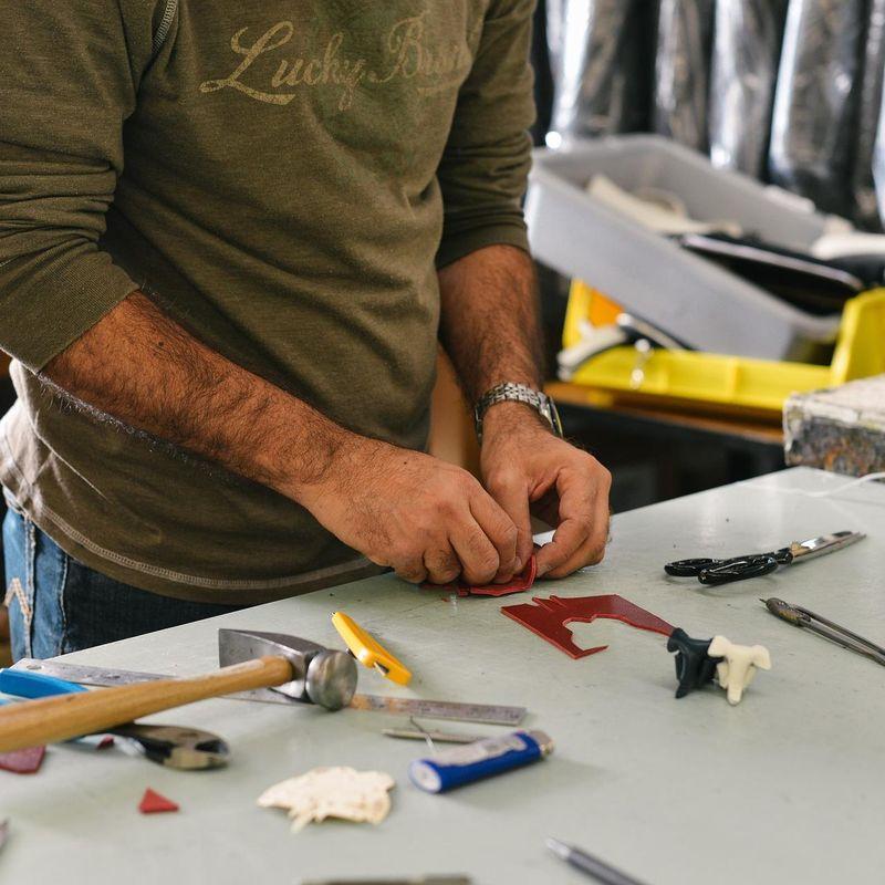 Ein Mann steht an einer Werkbank und formt ein rotes Stück Plastik. Auf der Werkbank liegen unter anderem Hammer, Schere, Lineal.