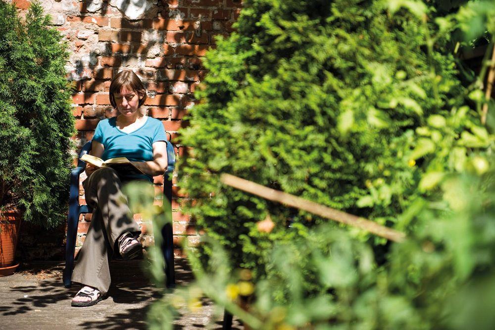 Eine Frau sitzt vor einem Haus im Grünen und liest.