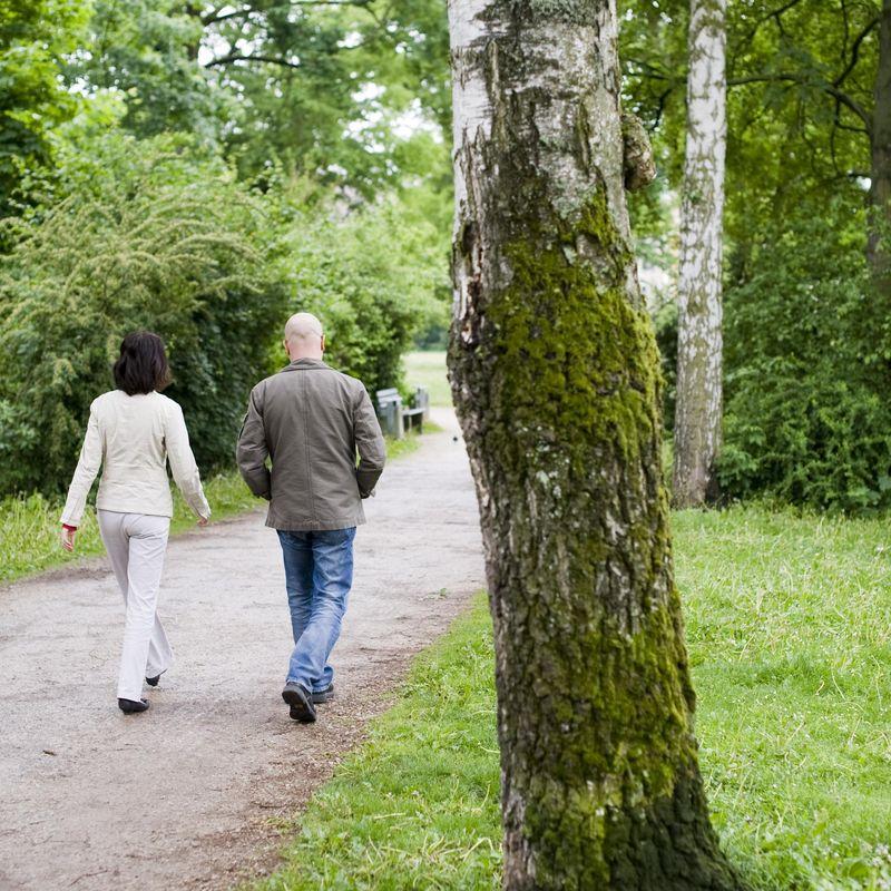 Eine Frau und ein Mann, die gemeinsam im Park spazieren gehen.