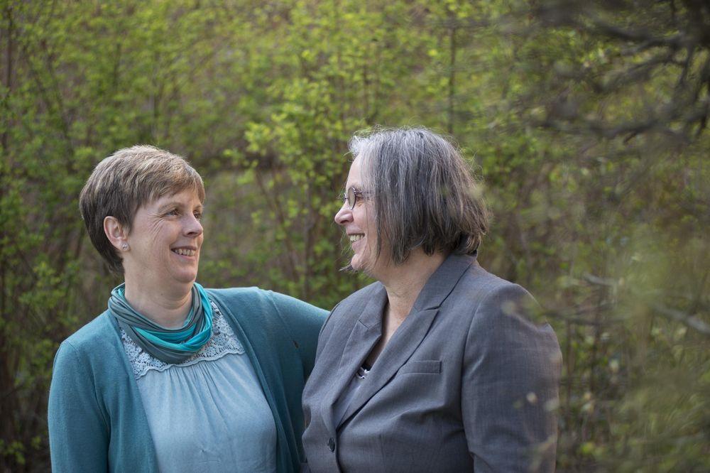 Zwei Frauen stehen im Grünen, die eine legt den Arm und die andere, beide lachen sich an.