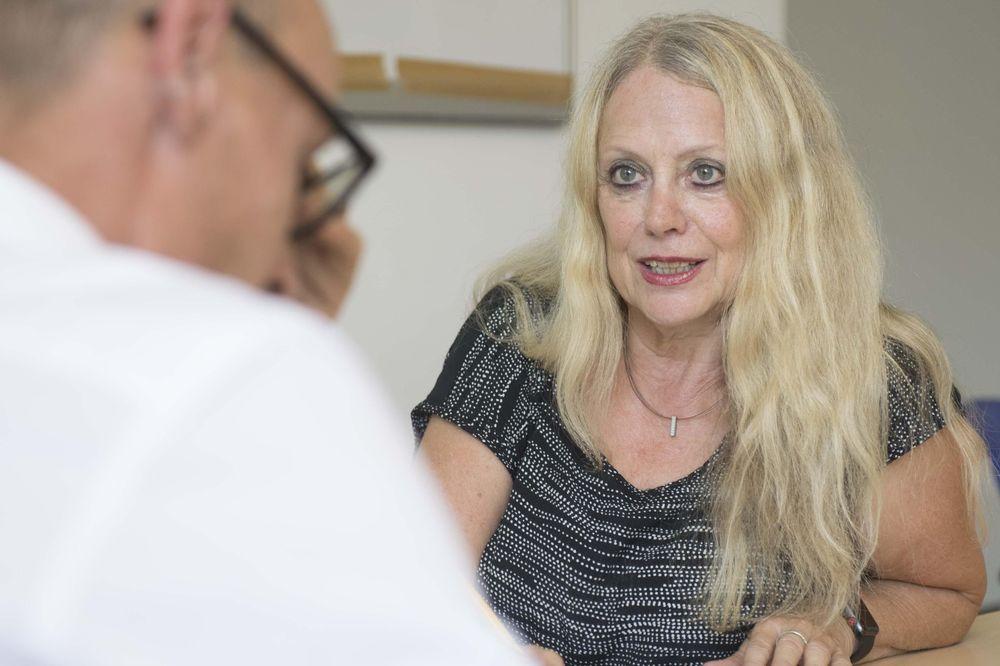 Eine blonde Frau und ein Mann mit Brille sitzen sich am Tisch gegenüber.