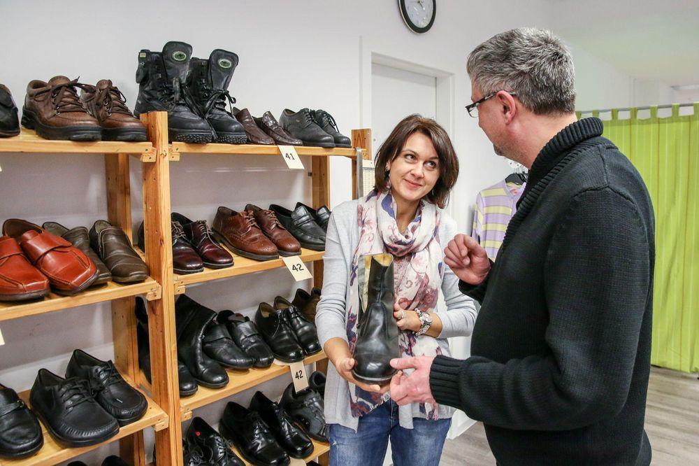 Verkaufssituation: Eine Frau zeigt einem Mann ein Paar Stiefel.