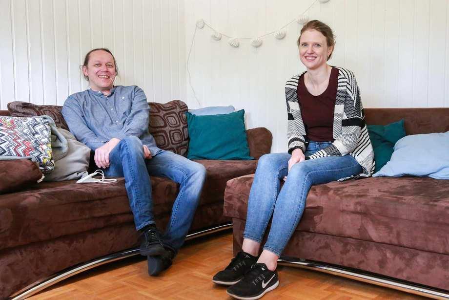 Ein Mann und eine Frau sitzen in einer Couch-Ecke. Sie lächeln.