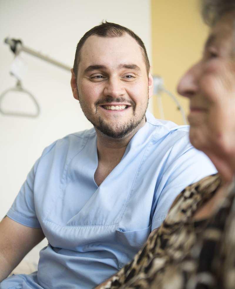 Ein Pfleger sitzt neben einer älteren Dame und lächelt.