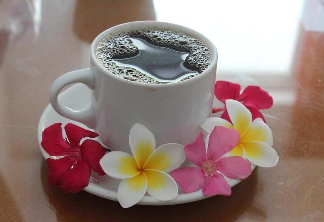 Eine Tasse mit Kaffee. Auf der Untertasse sind Blüten drapiert.
