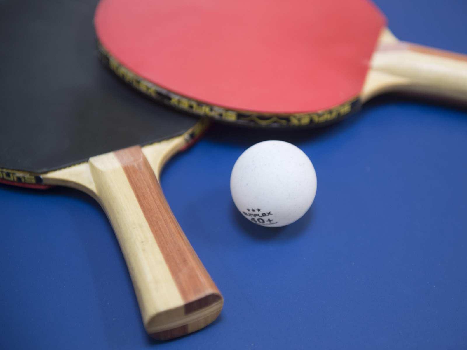 Zwei Tischtennisschläger und ein Ball auf einer blauen Platte