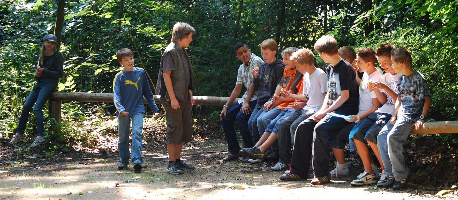 Eine Gruppe von Kindern, die auf einem umgefallenen Baum sitzen