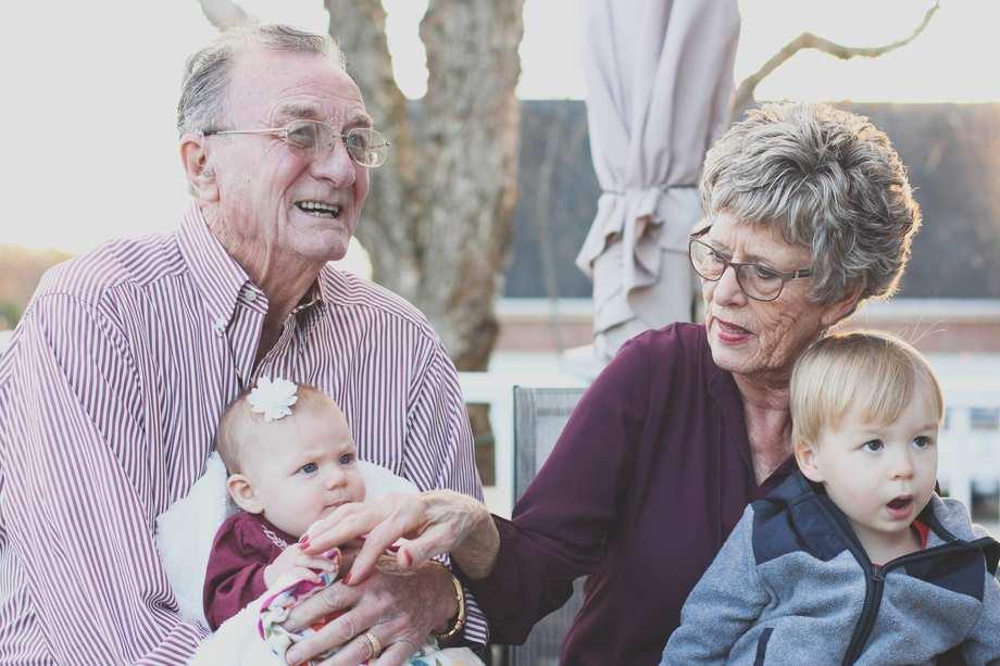 Ein älterer Mann und eine ältere Frau haben zwei Kleinkinder auf dem Schoß
