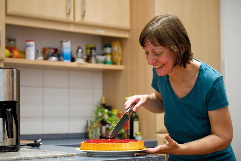 Eine Frau schneidet einen frischgebackenen Obstkuchen auf.