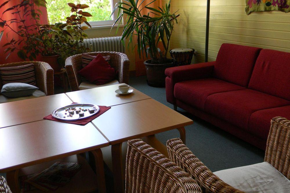 Ein Gemeinschaftsraum in dem ein Tisch und ein rotes Sofa steht.