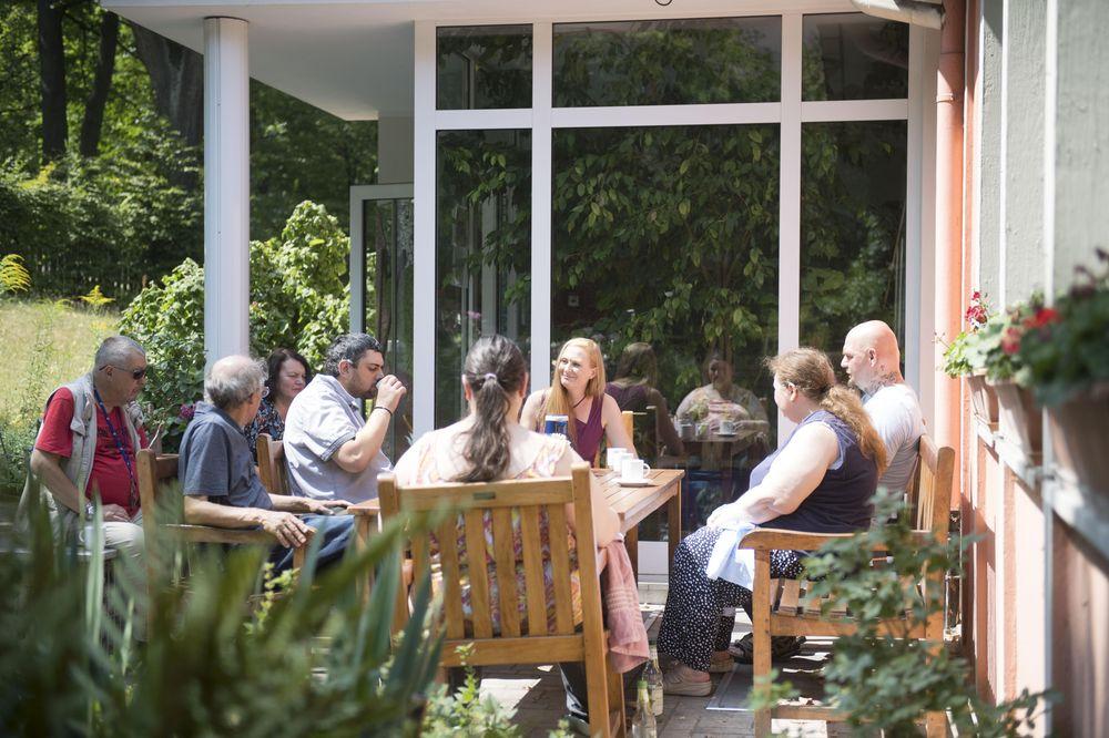Die Bewohner*innen sitzen vor dem Haus im Garten an einem großen Tisch und unterhalten sich.