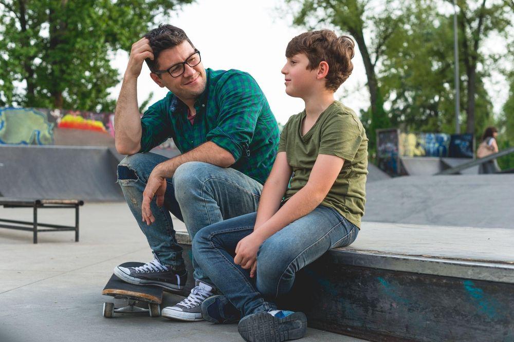 Ein Mann und ein Junge die am Skateplatz auf einer Rampe sitzen
