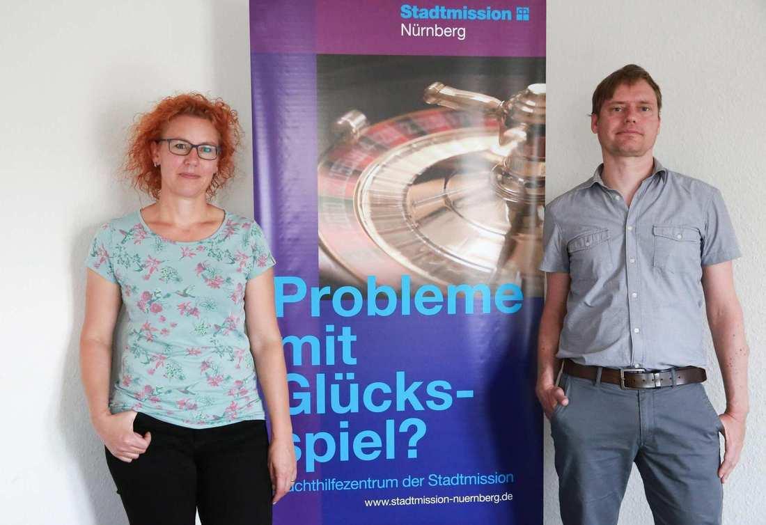 Eine Frau und ein Mann stehen vor einem Info-Banner.