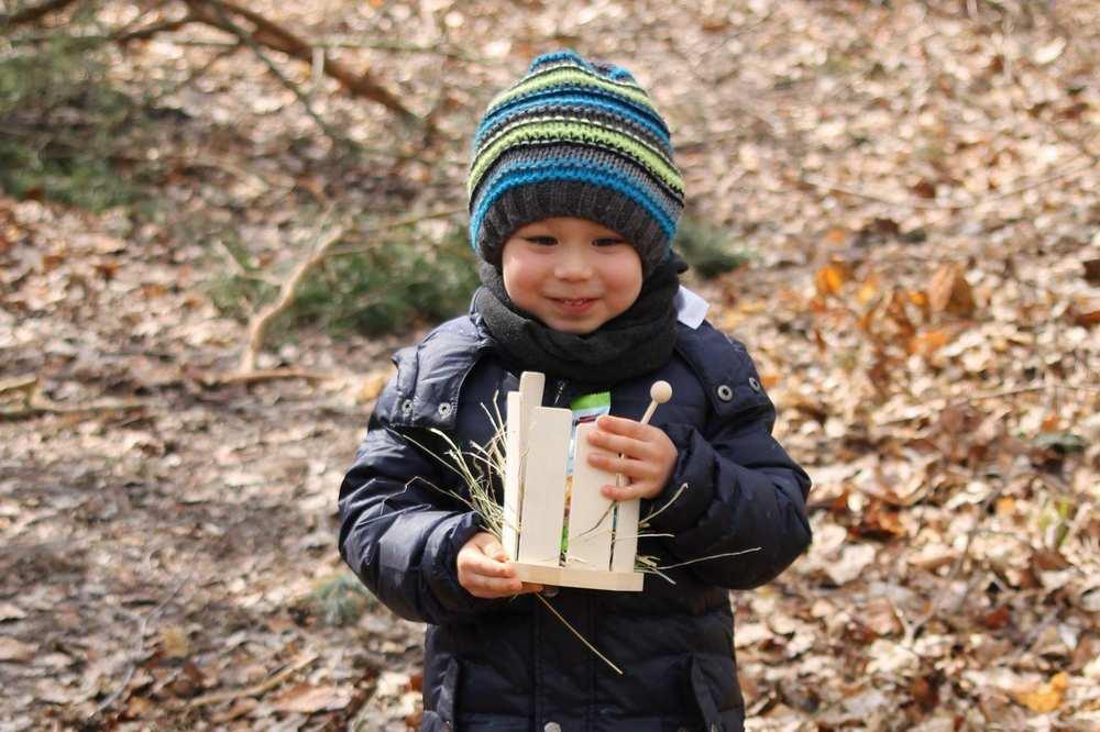 Ein warm gekleideter Junge trägt stolz sein Osternest durch den Garten mit Laub am Boden.