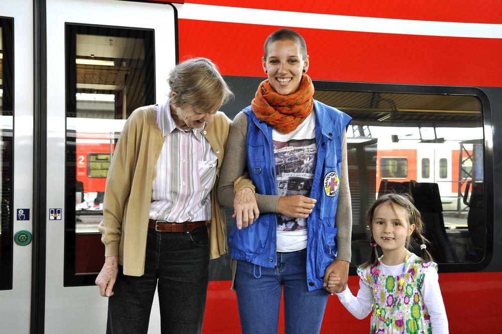 Eine alte Dame, eine junge Mitarbeiterin der Bahnhofsmission und ein kleines Mädchen stehen vor einem roten Zug. Die Dame henkelt sich bei der Helferin ein. Die Helferin hält das Mädchen an der Hand.
