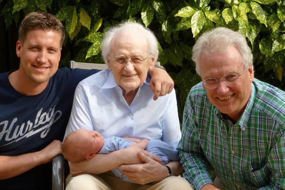 Vier Generationen sind auf einem Bild: Enkel (Baby), Vater, Großvater und Urgroßvater. Der Urgroßvater sitzt in der Mitte und hält das Baby.