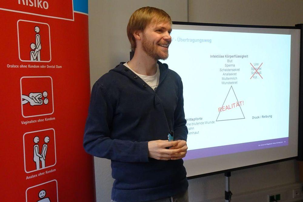 Ein Mann steht zwischen einem RollUp und einer Präsentation auf einer Leinwand.