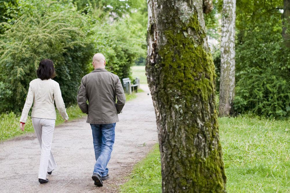 Eine Frau und ein Mann sind im park spazieren.