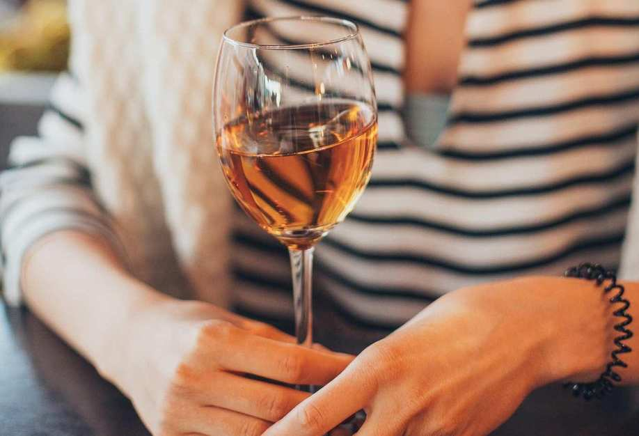 Frau mit langen Haaren hält sich an einem gefüllten Weinglas fest.