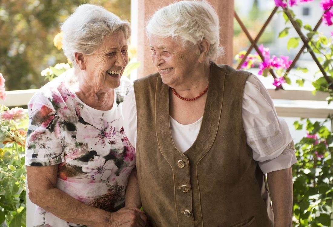 Zwei Seniorinnen stehen auf einem begrünten Balkon und lachen miteinander.