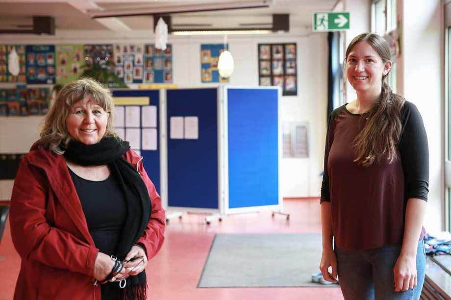 Eine ältere und eine junge Frau stehen in der Eingangshalle einer Schule.