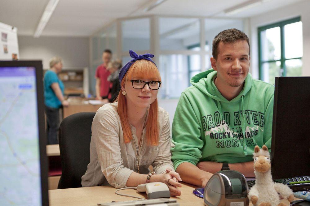 Ein junger Mann und eine junge Frau sitzen an einem Computer und lächeln in die Kamera.