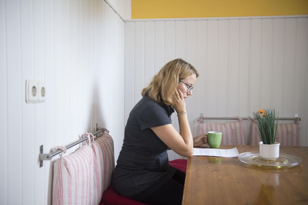 Eine Frau sitzt an einer Küchenbank und liest.