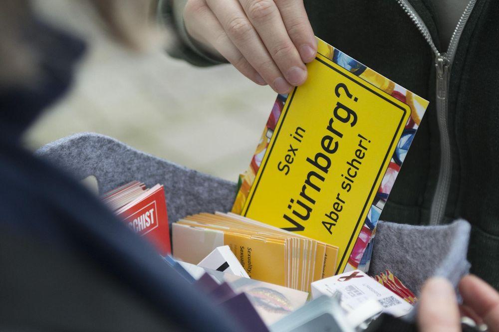 """Eine männliche Hand zieht aus einem Bauchladen ein Schild """"Sex in Nürnberg? Aber sicher!"""""""