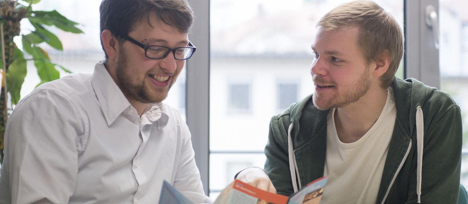 Zwei Männer schauen in einen Flyer und unterhalten sich darüber.