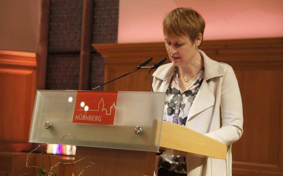 Eine Frau steht hinter einem Rednerpult.