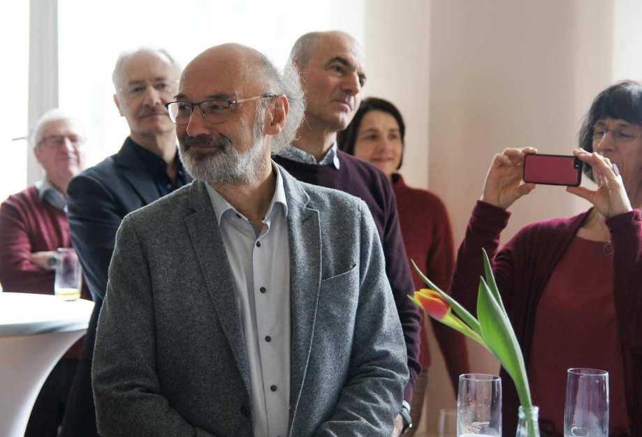 Ein Mann im grauen Tweet-Jacket schaut lächelnd nach links. Um ihn herum stehen Menschen und fotografieren.