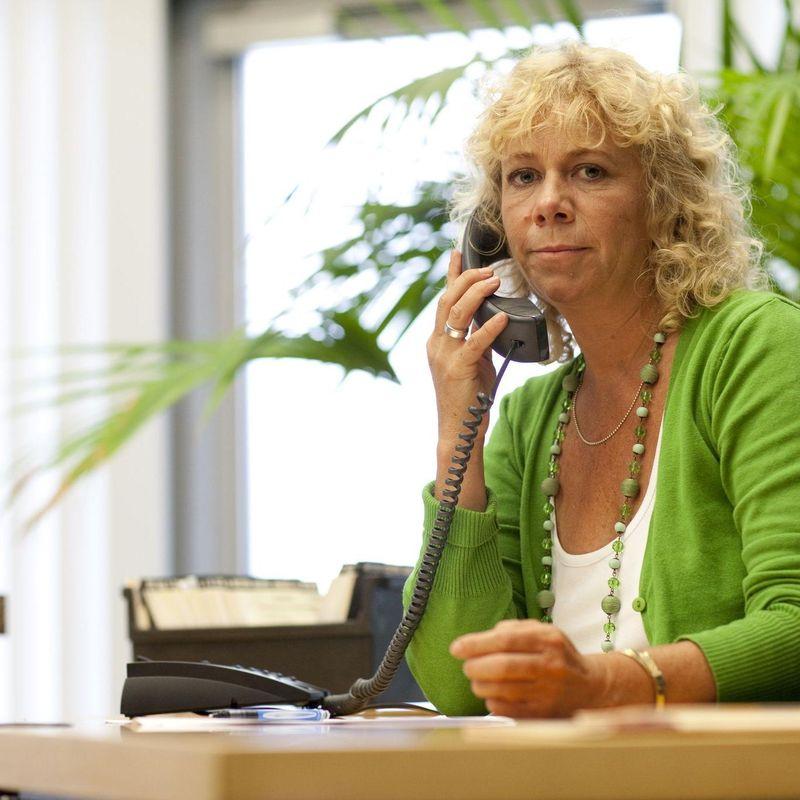 Eine blonde Frau sitzt an einem Schreibtisch und telefoniert.
