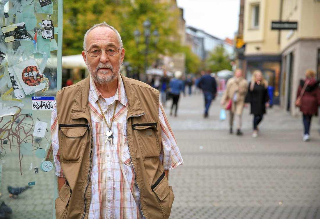 Ein älterer Mann mit weißem Haar, Brille und Dreitagebart in der Fußgängerzone. Er trägt ein kariertes Hemd und eine braune Weste.