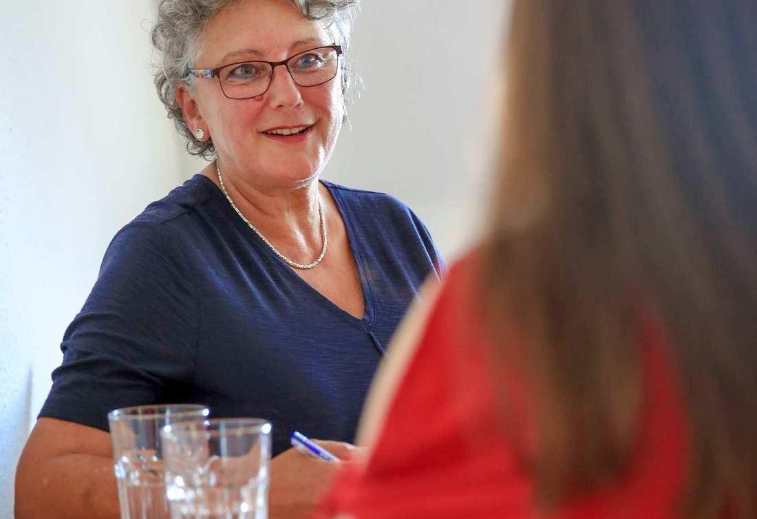 Eine Frau mit grauen Locken, Brille und blauer Bluse sitzt an einem Beratungstisch einer jüngeren Frau mit braunen Haaren gegenüber.