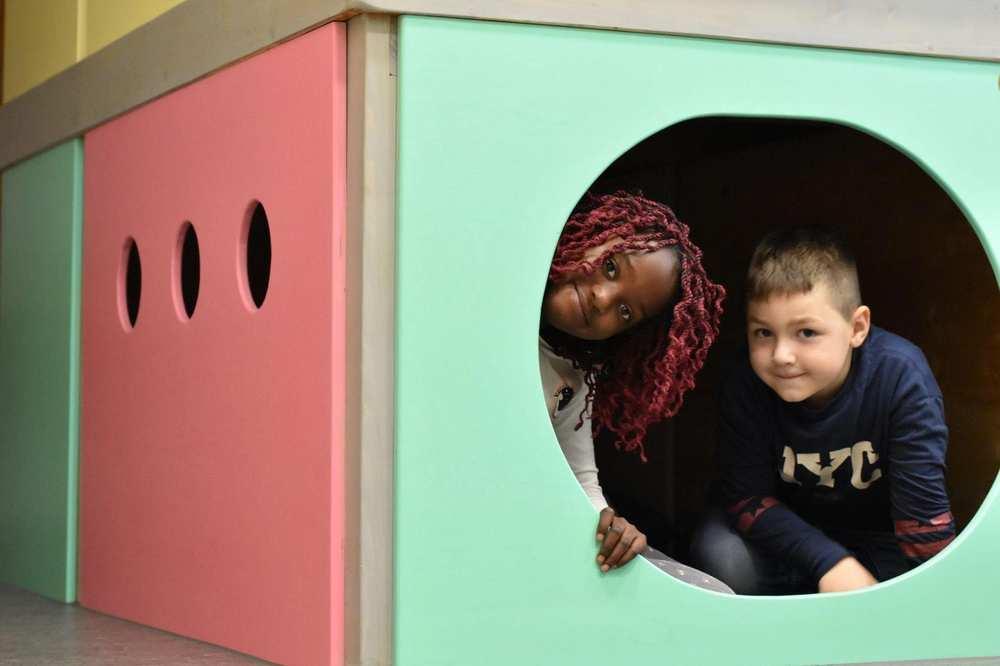 Zwei Kinder verstecken sich in einer Art Indoor-Höhle und schauen aus dem runden Loch.