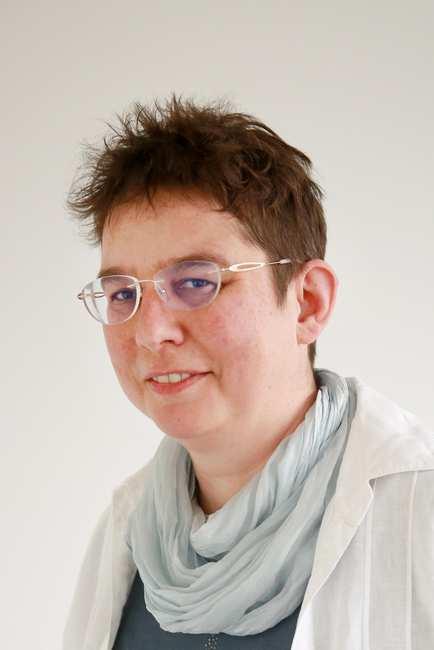Portrait einer Frau mit kurzen Haaren, Brille und hellem Schaal