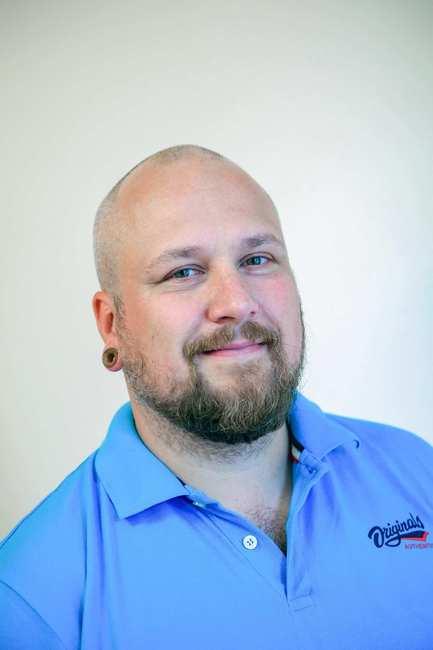 Ein Mann mit Glatze und Bart im blauem T-Shirt.