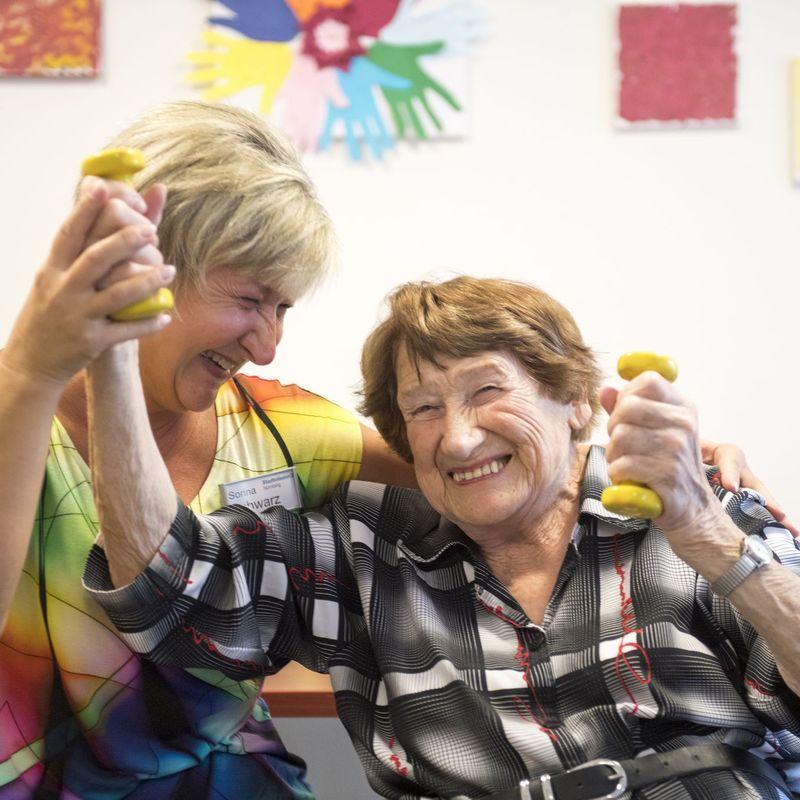 Eine Pflegerin macht mit einer Seniorin Gymnastik im Sitzen.