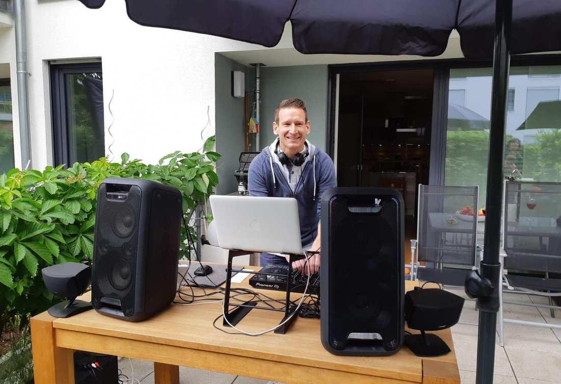 Hinter einem Tisch mit Laptop und Soundboxen steht Florian Dalferth mit Kopfhörern und lächelt.